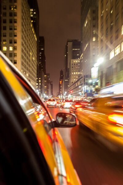 Taxi racing through city at night.